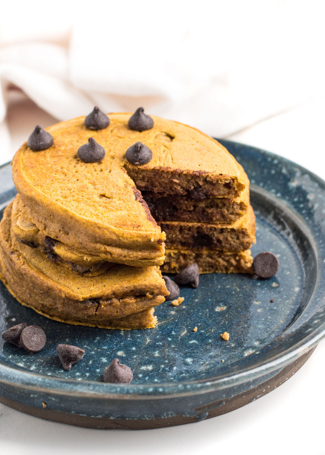 Deliciously fluffy Gluten Free Pumpkin Pancakes made fluffy and light with oat flour, pumpkin puree and lots of chocolate chips. These EASY one-bowl pancakes are perfect for a lazy weekend brunch or breakfast all week long.