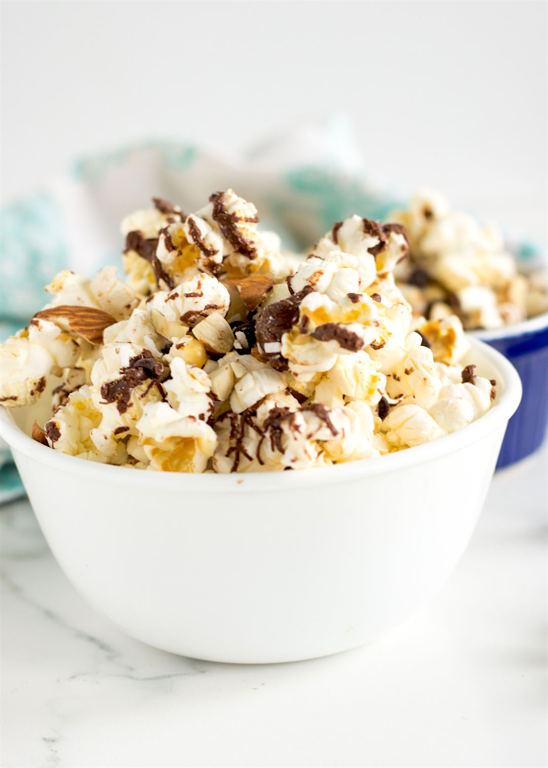 Light and fluffy homemade popcorn drizzled with dark chocolate and sprinkled with sea salt and mix together with nuts, more chocolate and coconut. This Salted Chocolate Popcorn Trail Mix is easy to make, gluten free, dairy free and vegan possible and it's a seriously good snack.