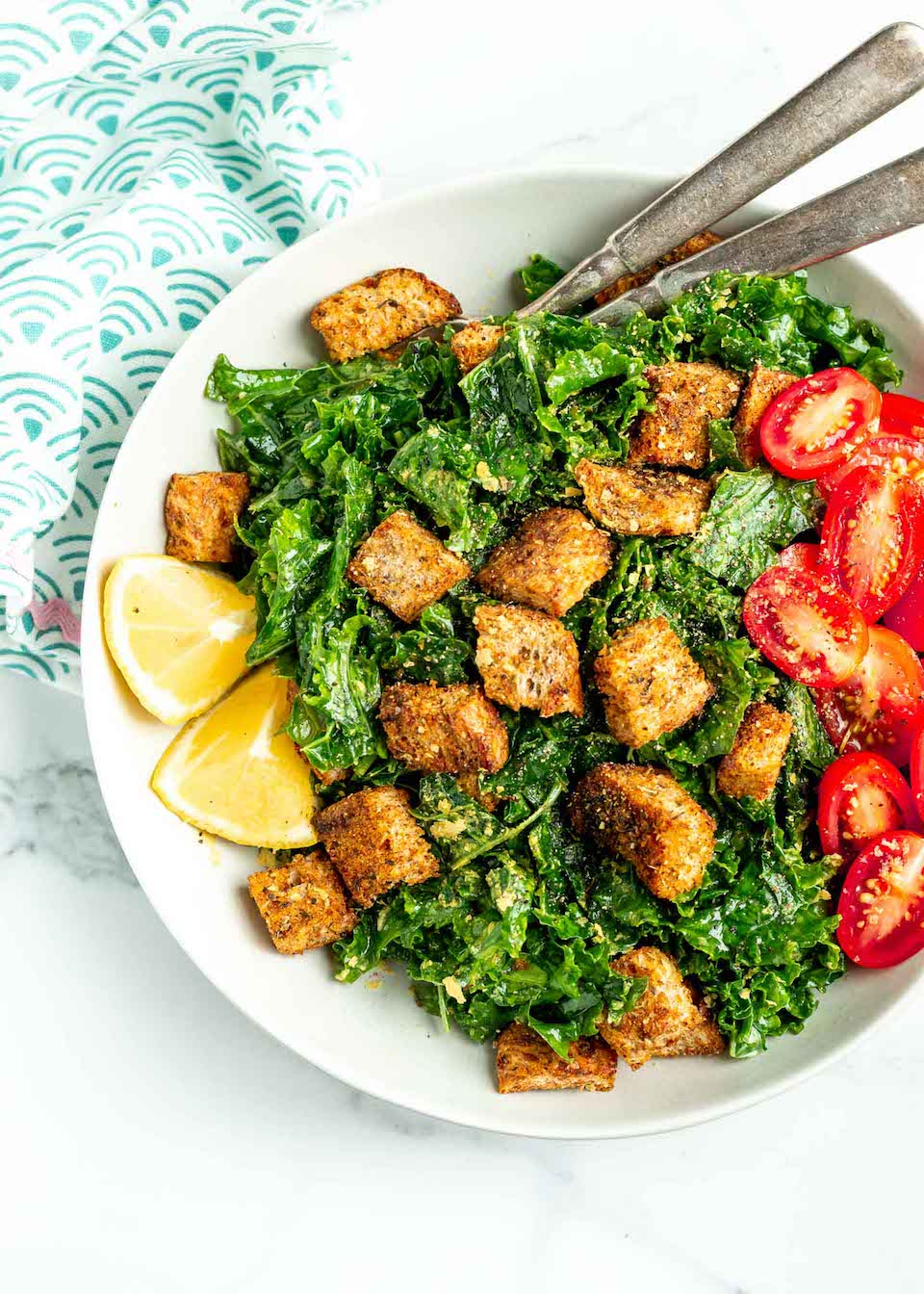This Easy Kale Caesar Salad is a lighter and vegetarian-friendly take on a classic! The perfect side dish beside any lunch or dinner, this healthy, clean eating (and gluten free!) chopped kale salad recipe is easy to make and tastes delicious! And the best part? A super simple caesar dressing made with lemon, olive oil and garlic and those homemade croutons!