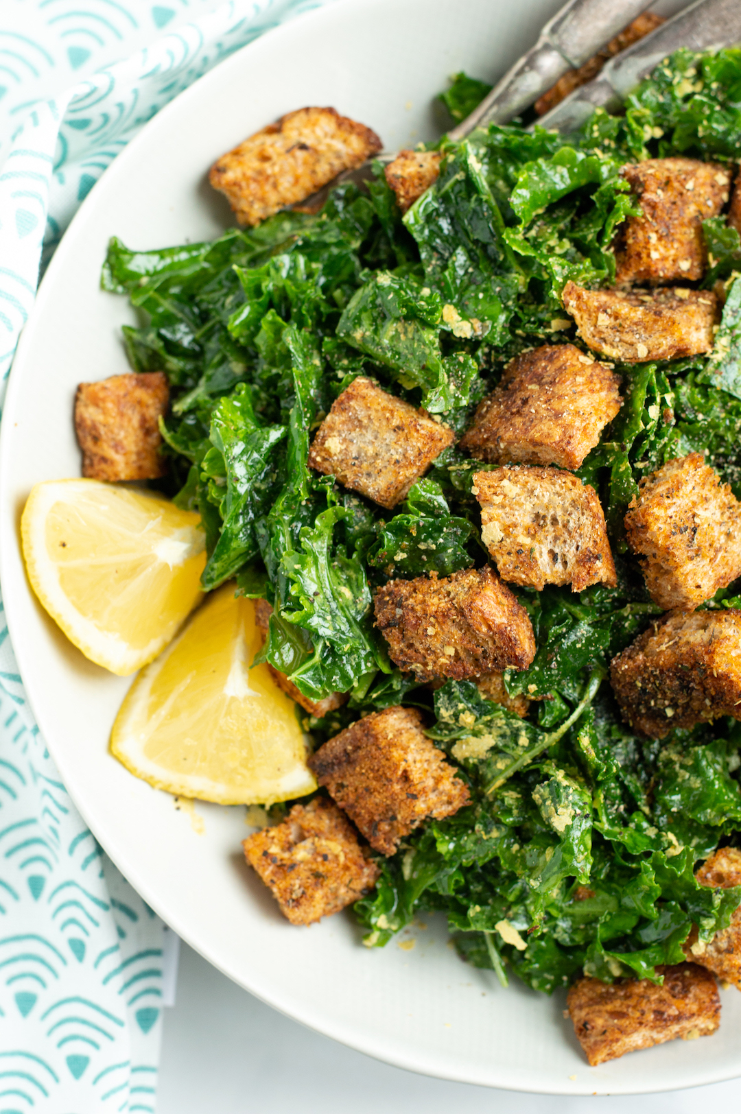 This Easy Kale Caesar Salad is a lighter and vegan take on a classic! The perfect side dish beside any lunch or dinner, this healthy, clean eating (and gluten free!) kale salad so good. And the best part? A super simple dressing made with lemon, olive oil and garlic and those homemade croutons!