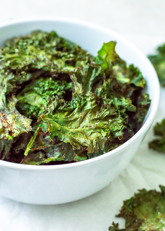 Crispy Garlic & Herb Kale Chips are the perfect snack. This oven-baked kale chip recipe uses a simple, homemade garlic and herb spice blend, curly kale and avocado oil for an easy, DIY veggie chip that actually tastes good!